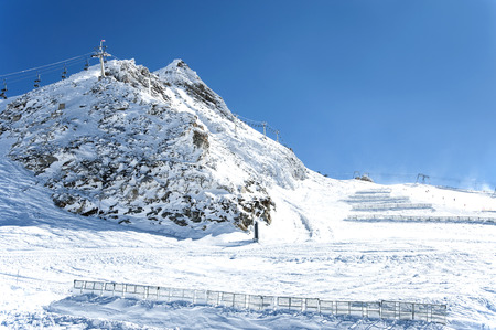 skiers: Ski lifts, snow fences and skiers on Hintertux glacier in Zillertal Alps in Austria Stock Photo