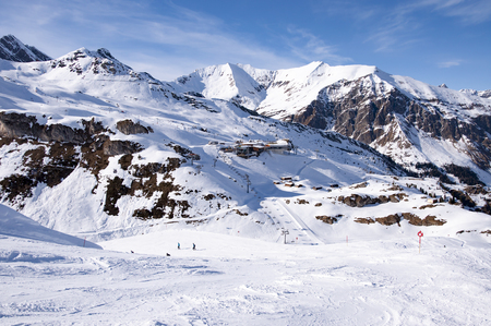 station ski: Zillertal Alps at Hintertux Glacier with a cable car station, ski lifts and pistes in sunset light