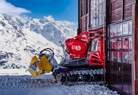 groomer: Red Snow groomer entering the garage in Austrian Alps Editorial