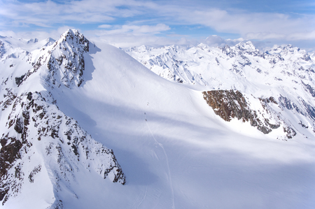A group of skiers wandering across a glacier in Alps in Italy viewed from Austria