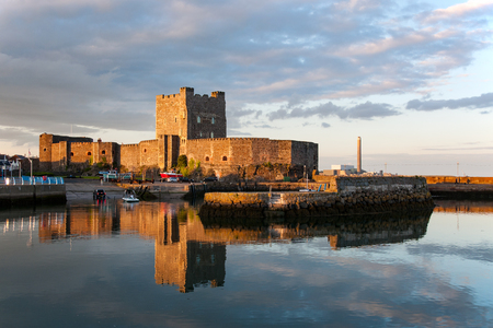 irish history: Medieval Norman Castle in Carrickfergus, Northern Ireland, and its reflection in water at sunset.