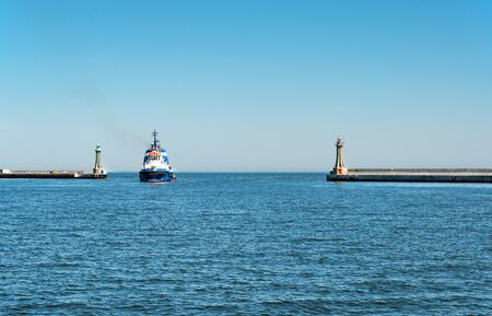 groyne: A tugboat entering the harbor in Gdynia, Poland