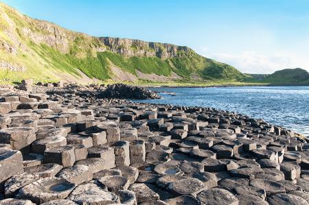 ジャイアンツコーズウェイ、岩と夕日の光の中の北アイルランド、アントリム郡で崖のユニークな地質学的形成