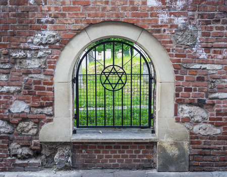 kazimierz: The Old historic  Remuh Cemetery in Kazimierz district in Krakow, Poland, established in 1535, viewed through the grille with the Star of David Stock Photo