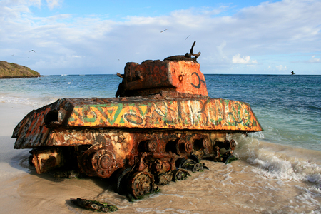 remnants: Old rusted and painted remnants of an US army tank on the Flamenco beach, Culebra Island, Puerto Rico