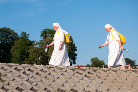 nuns: KRAKOW, POLAND - JULY 29, 2016: World Youth Day 2016. Two women, female pilgrims, nuns in white habits, walking along the river embankment with yellow backpacks and bottles with water