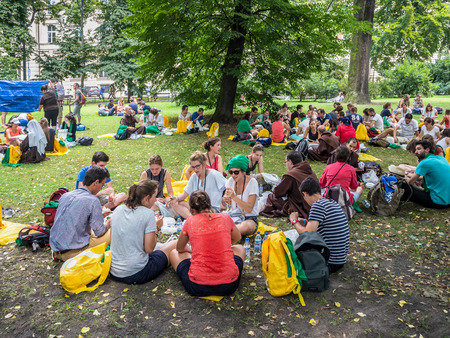 KRAKOW, POLAND - JULY 29, 2016:. World Youth Day 2016. Young people from various countries sitting on the ground, resting, eating, drinking and talking in small groups in Planty Park in Cracow near the railway station Editorial