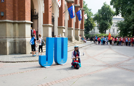collegium: KRAKOW, POLAND - JULY 27, 2016: World Youth Day 2016: A girl making a selfie and other young pilgrims in front of the Collegium Novum of Jagiellonian University in Cracow Editorial