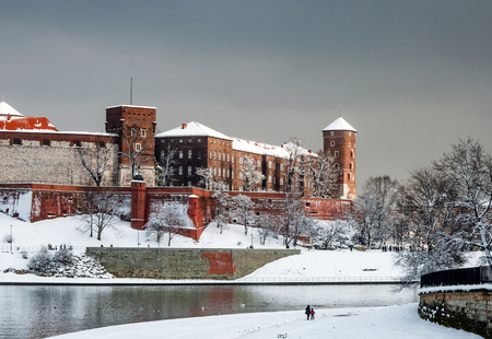 Fragment of historic royal Wawel Castle with Sandomierska Tower and defensive wail in Cracow, Poland, with Vistula River and walking people on cloudy day in winter in last sunlight before the snowfall