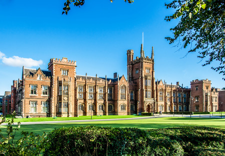The Queens University of Belfast with a grass lawn, tree branches and a hedge in sunset light