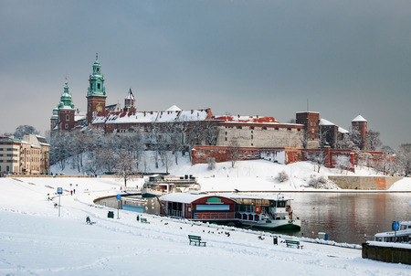 Historic royal Wawel Castle and Cathedral in Cracow, Poland, with Vistula River and harbor on a cloudy day in winter in last sunlight before the snowfall