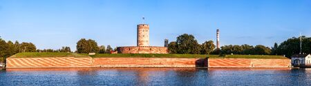 Medieval Wisloujscie Fortress with old lighthouse tower in port of Gdansk, Poland. A unique monument of the fortification works. Wide panorama in sunset light.
