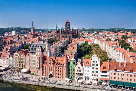 Gdansk Old City in Poland with Gothic St Mary church, Mariacka Gate, City Hall tower, historical houses and the promenade along the riverbank of Motlawa river. Aerial view.
