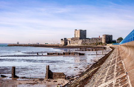 lough: Medieval Norman Castle in Carrickfergus near Belfast, Northern Ireland, and Belfast Lough during a low tide Stock Photo
