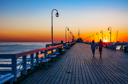 Sunrise at the wooden pier (molo) in Sopot, Poland and a unrecognizable walking couple Stock fotó