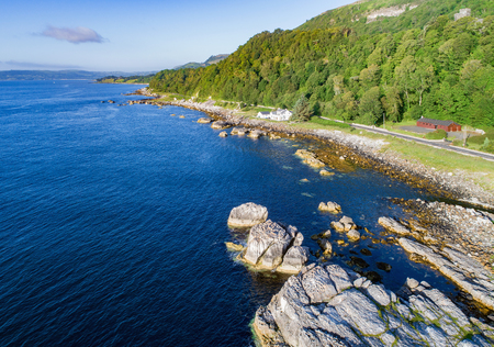 The eastern coast of Northern Ireland and Antrim Coastal Road, a.k.a. Causeway Coastal Route. Aerial view at sunrise