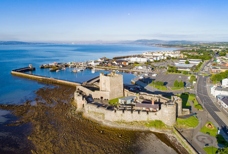 Medieval Norman Castle in Carrickfergus near Belfast in sunrise light. Aerial view with marina, yachts, parking, town and far view of Belfast in the background. Editorial