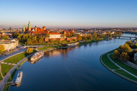 Panorama sur Skyline de Cracovie, en Pologne, avec le château royal de Wawel, la cathédrale, la Vistule, le pont, le port, les bateaux et le restaurant à bord. Vue aérienne à l'automne dans la lumière du coucher du soleil.