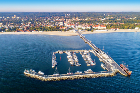 Sopot resort in Poland. Wooden pier (molo) with marina, yachts, pirate tourist ship,  beach, vacation infrastructure, hotels, park and promenade. Aerial view at sunrise.