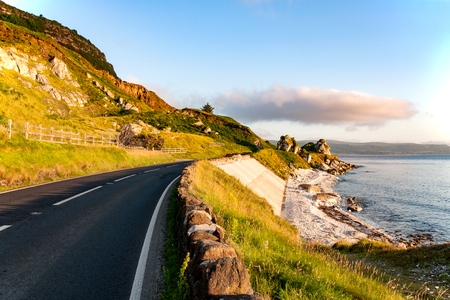 The eastern coast of Northern Ireland and Antrim Coastal road a.k.a. Causeway Coastal Route wit rocks and concrete revetment in sunrise light