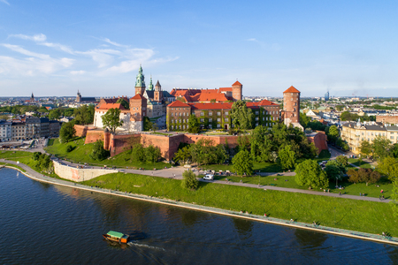 Krakow, Poland. Wawel hill with historic royal castle and cathedral, Vistula River, tourist boat, park and walking people. Aerial view in summer at sunset. 新闻类图片