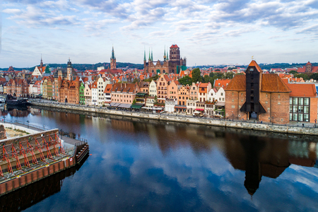Gdansk old city in Poland with the oldest medieval port crane (Zuraw) in Europe, St Mary church, Town hall tower and Motlawa River. Aerial view, early morning