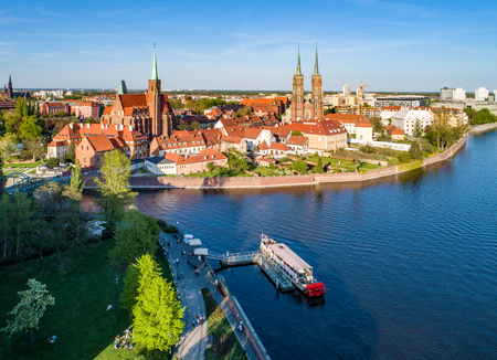Poland. Wroclaw. Ostrow Tumski, Gothic cathedral of St. John the Baptist,  Collegiate Church of the Holy Cross, Archbishops palace, tourist harbor, ship and Odra (Oder) River. Aerial view at sunset Stock Photo