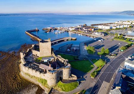 Castello medievale normanno a Carrickfergus vicino a Belfast nella luce dell'alba. Vista aerea con marina, yacht, parcheggio, città e vista lontana di Belfast in background.