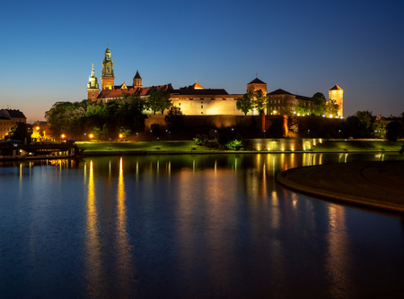 Poland, Krakow. Illuminated royal Wawel castle and cathedral at night and light reflections in Vistula River. Riverside with park, trees, promenade, lanterns, harbor and tourist ship