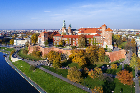 Krakow, Poland, with royal Wawel castle, cathedral and Vistula river in autumn. Aerial skyline panorama at sunset.