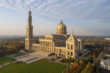 Sanctuary and Basilica of Our Lady of Licheń or Our Lady of Sorrows in small village Lichen. The biggest church in Poland, one of the largest in the World. Famous Catholic pilgrimage site. Aerial view in fall in sunset light Stock Photo