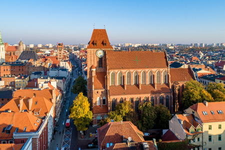 Medieval Gothic Cathedral of St. John in Torun, Poland, and old city with town hall tower.