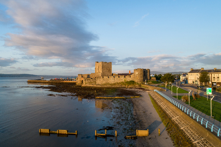 Medieval Norman Castle in Carrickfergus near Belfast in sunrise light. Aerial view with marina, yachts, groyne, and Belfast Lough.