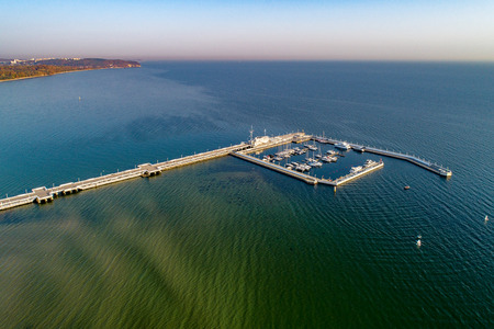 Poland, Sopot resort. Wooden pier (molo) with marina, yachts, sailboats and promenade. Far view of Gdynia in thw background. Aerial view in sunrise light Zdjęcie Seryjne