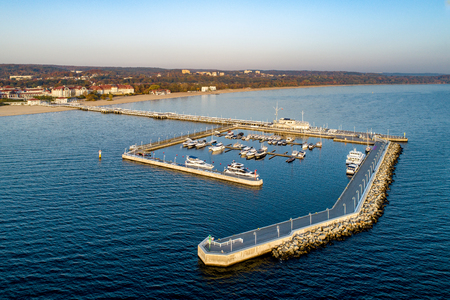 Poland, Sopot resort. Wooden pier (molo) with marina, yachts, sailboats, beach, vacation infrastructure, hotels, park and promenade. Aerial view at sunrise