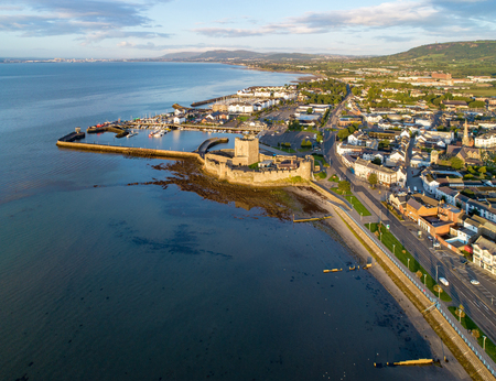 Belfast Lough. Medieval Norman Castle in Carrickfergus  in sunrise light. Aerial view with marina, yachts, parking, breakwater, groin, sediments and far view of Belfast in the background