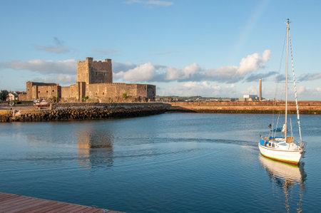 Medieval Norman Castle, yacht, harbor, breakwater and power plant in Carrickfergus near Belfast, Northern Ireland, UK, in sunset light
