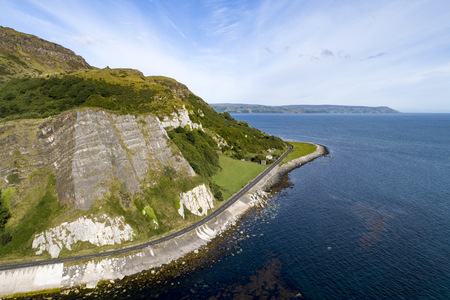 Northern Ireland, UK. Atlantic coast. Cliffs and A2 Antrim Coast Road, a.k.a. Giants Causeway Coastal Route. One of the most scenic coastal roads in Europe. Aerial view near Garron Point Zdjęcie Seryjne