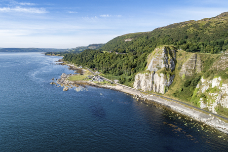 Garron Point in Northern Ireland, UK. A geological formation, parking and marina at Antrim Coast Road, a.k.a. Giants Causeway Coastal Route. One of the most scenic coastal roads in Europe. Aerial view