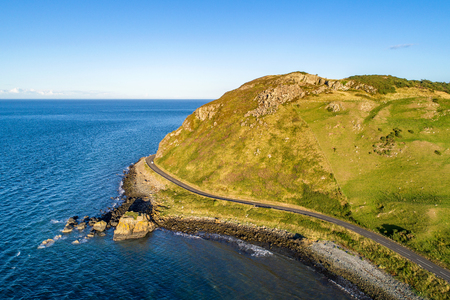 Northern Ireland, UK. Causeway Coastal Route a.k.a Antrim Coast Road near Ballygalley Head and resort. One of the most scenic coastal roads in Europe. Aerial view