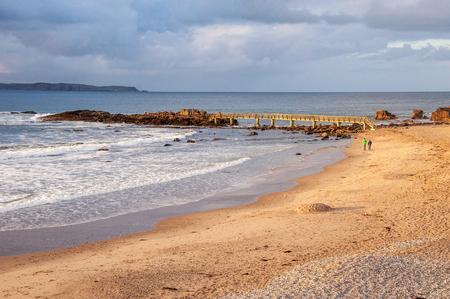Ballycastle, Northern Ireland, UK. Atlantic coast. Beach with bridge, island, rocks, waves and unrecognizable waking pair in sunset light with dark heavy clouds Zdjęcie Seryjne