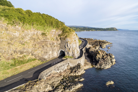 Causeway Costal Route with Black Arc tunnel. Scenic road along eastern coast of County Antrim, Northern Ireland, UK. Aerial view in sunrise light