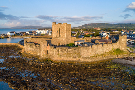 Medieval Norman Castle in Carrickfergus near Belfast in sunrise light. Aerial view with marina, sediments town and Belfast Lough