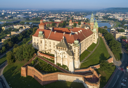 Historic royal Wawel castle and cathedral in Cracow, Poland.  Aerial view in sunrise light early in the morning. Vistula River with Debnicki Bridge in the background
