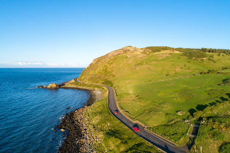 Northern Ireland, UK. Causeway Coastal Route a.k.a Antrim Coast Road near Ballygalley Head and resort with red cars. One of the most scenic coastal roads in Europe. Aerial view.