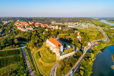 Sandomierz, Poland. Medieval gothic castle in front, old town with town hall tower,  gothic cathedral and Vistula river in the background. Aerial view in sunset light Publikacyjne