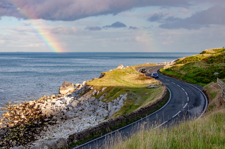 The eastern coast of Northern Ireland and Antrim Coastal Road, a.k.a. Causeway Coastal Route with cars and rainbow in sunset light Zdjęcie Seryjne