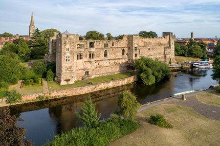 Ruins of medieval Gothic castle in Newark on Trent, near Nottingham, Nottinghamshire, England, UK. Aerial view with Trent River in sunset light.