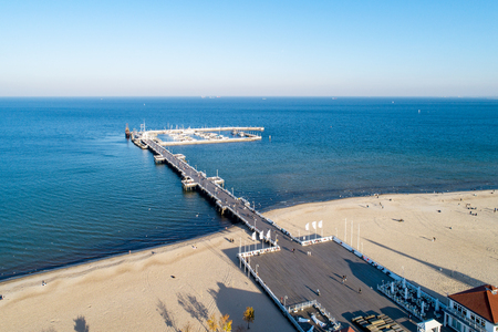 Wooden pier with harbor, marina with yachts and beach in Sopot resort near Gdansk in Poland in sunset light. Aerial view