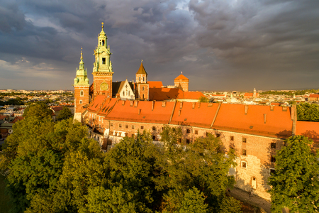 Historic royal Wawel Cathedral and castle in Cracow, Poland.  Aerial view in sunset light with dark stormy clouds Publikacyjne